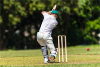 A batsman swinging and missing the ball