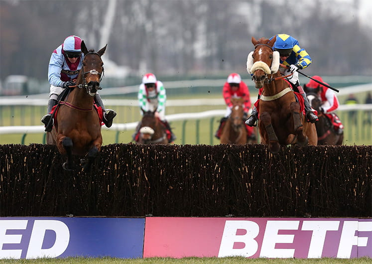 Horses approaching a hurdle at the Betfair Grand National
