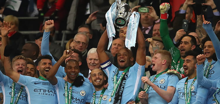 Manchester City players lifting the Trophy