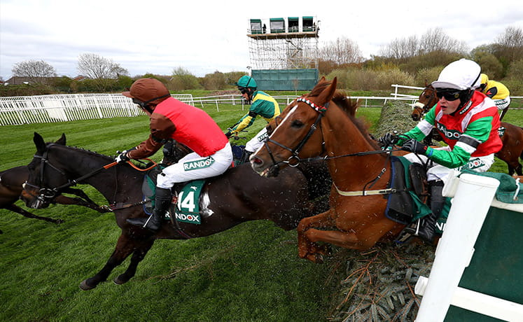 Horses jumping a hurdle at the Grand National