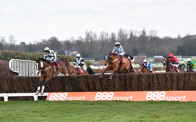 Horses jumping a hurdle at Kempton